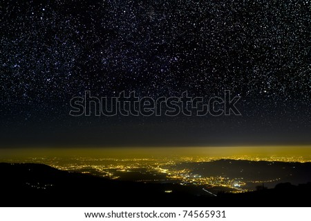 The Universe above city lights. The dark night sky.
