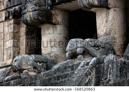 The upper level of the Temple of the Jaguars with the carved heads of Kukulcan, facing the great Ball Court in Chichen Itza, Yucatan, Mexico. #568520863