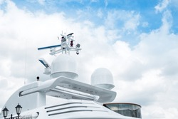 the upper part is the roof of a luxurious white yacht against a cloudy sky