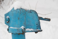 The upper part of a castiron water column unevenly painted in blue, snow, winter