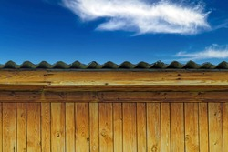 The upper part of the outbuilding on the background of the blue sky with white clouds