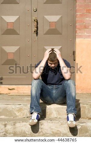 The upset man sits on the stairs near the house door