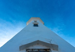 The upward view of a vintage white concrete lighthouse with multiple small closed glass windows. At the top of the octagon shaped building are a watch room and lantern. The background is a bright blue