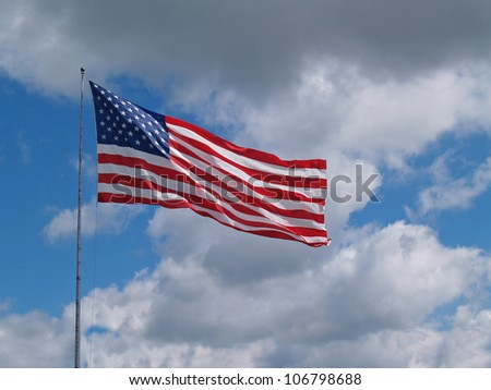 The US American red, white and blue flag flying in front of a blue cloudy sky.