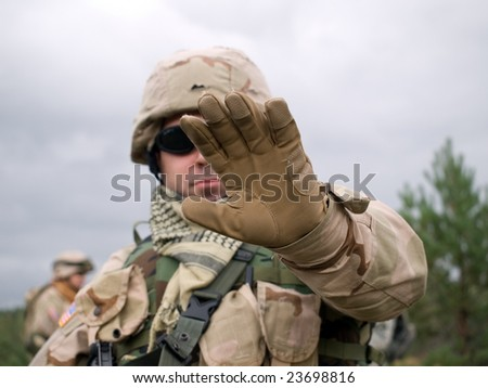 The US Soldier showing arm to stop some action (for example, filming or walking, etc.)