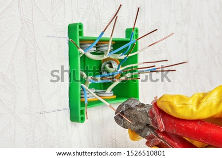 The use of end nippers for cutting the ends of copper wires during installation of a plastic rectangular electrical junction box and home electric wiring. Electrician uses wire cutters. #1526510801