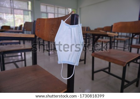 The used medical face mask hangs on the wood lecture chairs in the empty classroom. Concept during the Coronavirus Disease COVID-19 outbreak and pandemic in the 2020s. Back to school concept.