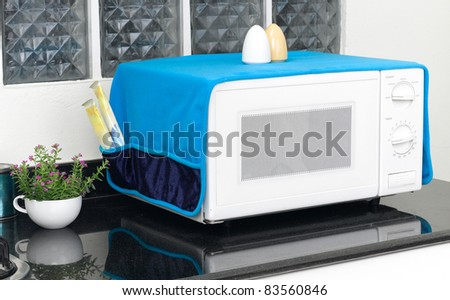 The used microwave oven with the cover blanket to protect dust or dirty