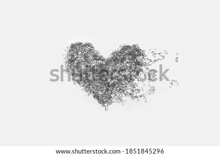 The used staples are placed as a heart shape on white background. Stockfoto ©