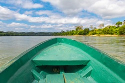 The Usumacinta river, the international border between Guatemala and Mexico, seen from a boat. Boat is sharp, rainforest and riverbank unsharp.