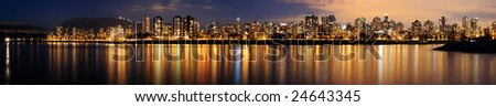 The Vancouver downtown at night glittering against a backdrop of dark mountains. - stock photo