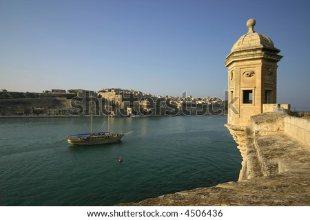 The Vedette in Senglea,Malta with a tourist schooner cruising along with Valletta in the background