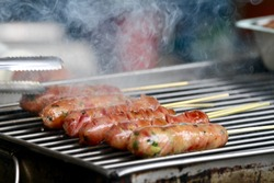 The vendor sells grilled sausage and the heavy smoke. The traditional Taiwan snack and food.
