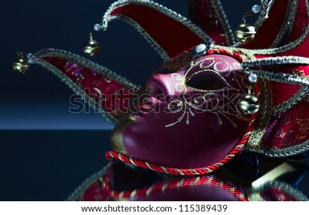 The Venetian mask with bells on a mirror table