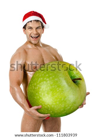the very muscular  bronzed handsome sexy Santa Claus on white  background, hold great green apple and laughing, isolated