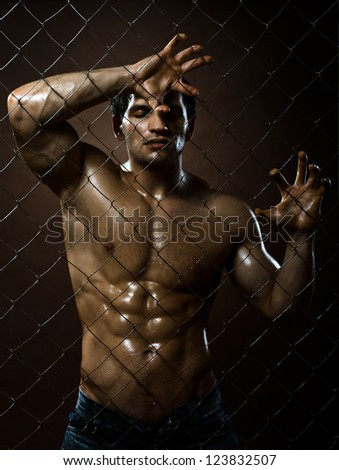 the very muscular handsome sexy guy, on netting steel fence