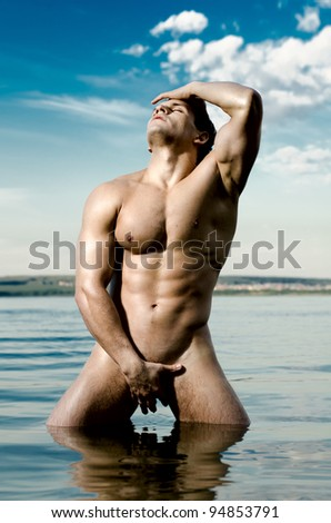 the very muscular handsome sexy guy on sky and sea background