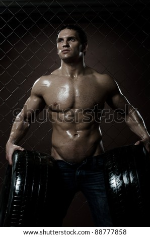 the very muscular handsome sexy guy with rubber-tire,  on  netting  steel fence background