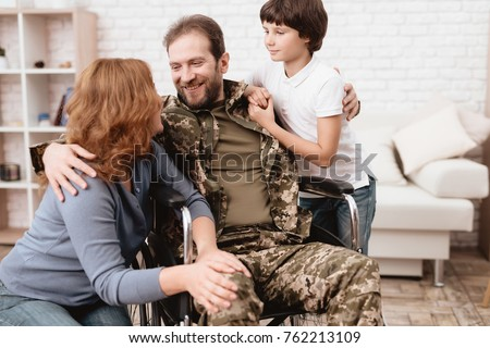 The veteran in a wheelchair came back from the army. Wife and son are glad to see him. A man in uniform in a wheelchair with his family.
