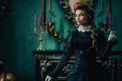 The Victorian era concept. Beautiful woman in elegant historical dress and hairstyle posing in vintage interior. Baroque. Fashion.