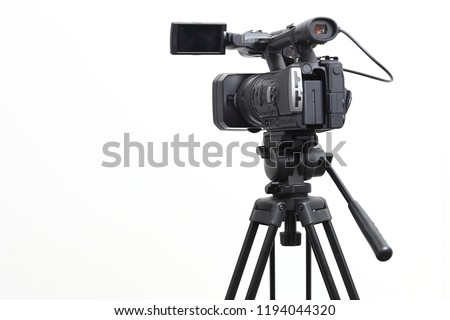 The video camera with the microphone is standing on the tripod isolated on white, in concept of technology, modern, entertainment.