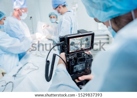 The videographer shoot the surgeon and assistants in the operating room with surgical equipment. Medical background