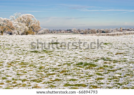the view across frosty fields toward the village