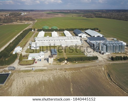 The view from the height of a large farm located among the green hilly fields. Video from a drone or a quadro. Agro-industrial complex with stainless steel silo. Organic food production.Dairy industry Foto stock ©