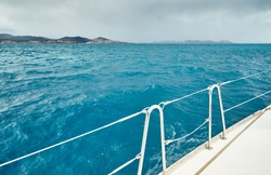 The view from the sailboat on the sea and mountains, a boat Board, slings and ropes, a sail, splashes from under the boat, improbable azure water, comes nearer a storm