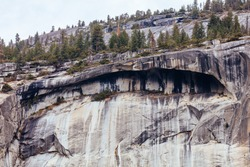 The view from within Yosemite Valley and rock detail of surrounding rock faces on a stormy day in California, USA
