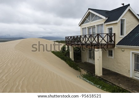 The view of a beach house right next to the sand dunes, Witsand, South Africa