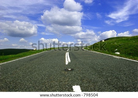 The view of a mountain road  with a right hand bend in the distance against a blue sky with white clouds.