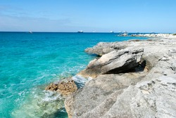 The view of erdoded Grand Bahama island coastline and cargo ships in a background (Bahamas).