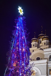 The view of  illuminated new year tree on the background of St. Nicholas church (Cultural and educational center Tsarsky) at night. Yekaterinburg. Russia