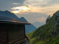 The view of Rifugio Prandini Franco with mountains on background in twilight, Braone Valley, Lombardy, Italy.