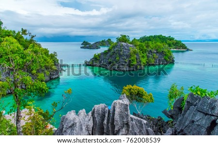 Stock Photo the view of rocky islands, cliffs and lagoon at Kimaboe Hills and Lagoon, Labengki, Southeast Sulawesi, North Konawe, Indonesia, with clear and bright sea water, clear blue sky and clouds