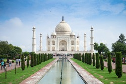 The view of symmetry Taj Mahal on central axis pool in blue sky