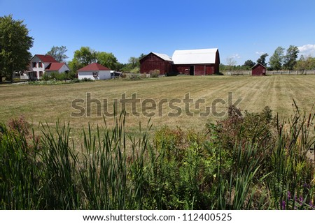 The view of the farm house and barn on the blue sky and green grass background