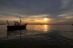The view of the sky after sunset is beautiful with the reflection of the fishing boat in the sea in Thailand.