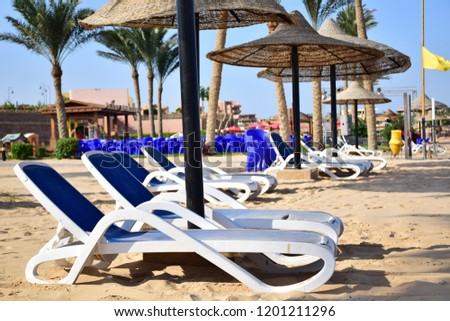 the View of Umbrella and Sea chairs on the sand and beach in background  with cloudy sky in Sunny day  from resort in Egypt / the best destination for holidays.