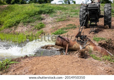 The view of water gushing violently from large old steel pipes and agricultural vehicles on a mound into green rice fields is common in rural Thai agriculture. ストックフォト ©