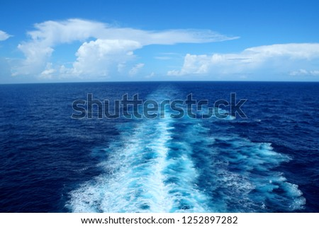 The view of waves and blue ocean from behind a cruiseship