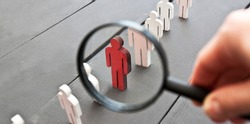 The view through the magnifier on the one wooden red person between other people