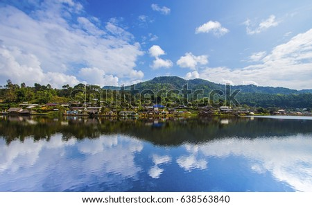 Shutterstock The village next to the river. The backdrop has mountains and beautiful blue turquoise sky. The river has a beautiful reflection. Village in Pai, Mae Hong Son, Thailand