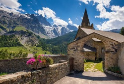 The village of La Grave and its church in the Ecrins National Park with La Meije peak. Summer in the Oisans Massif. Hautes-Alpes, French Alps, France