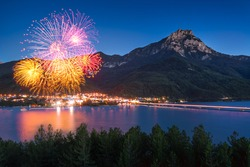 The village of Savines-le-Lac with 14th of July fireworks (Bastille Day celebration). Serre-Poncon Lake in summer at twilight. Hautes-Alpes, France