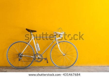 The vintage  hybrid bicycle parking against yellow wall