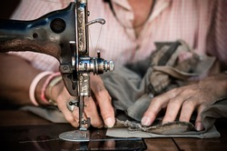 The vintage sewing machine on old man designer blur background,vintage color tone