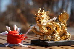 The virus figurine holds a rope binding the dragon figurine in its hand. A concept symbol.