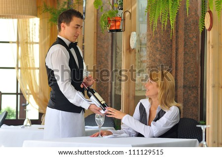 The waiter at the restaurant offers wine visitor - stock photo